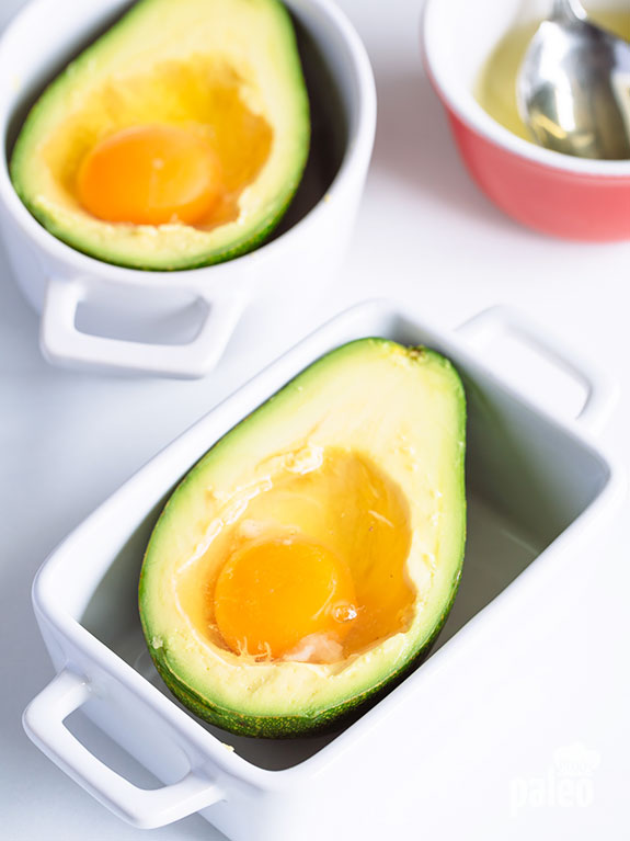cracked eggs in halved avocado