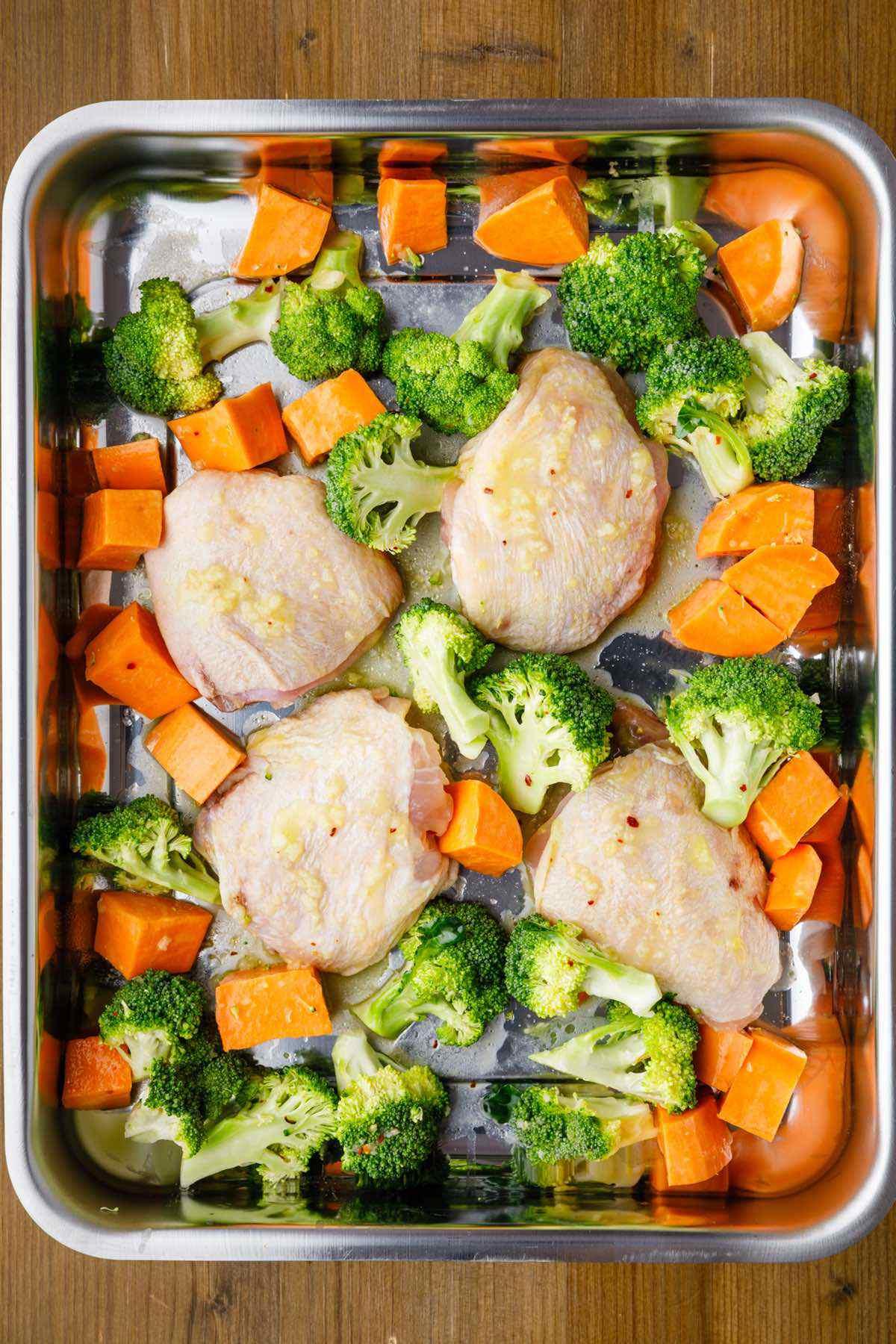 prepping raw chicken thigh broccoli sweet potato